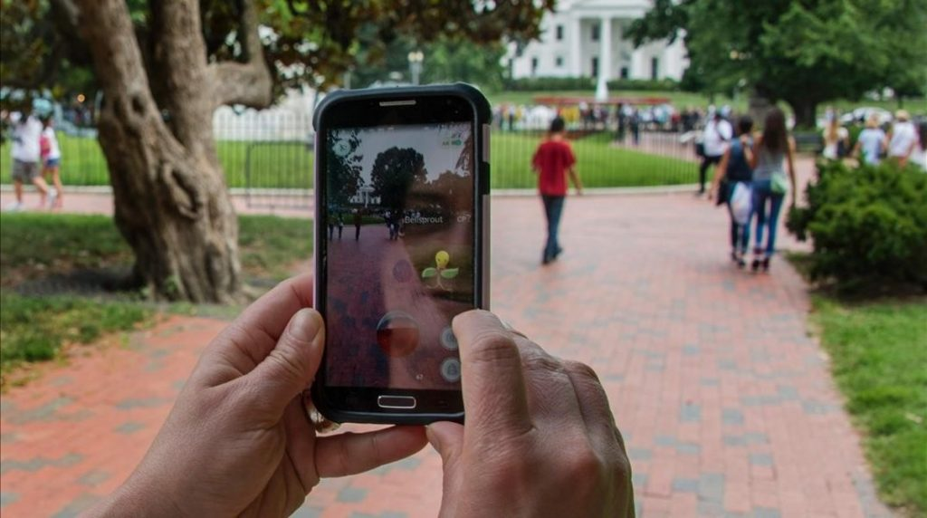 A woman holds up her cell phone as she plays the Pokemon Go game in Lafayette Park in front of the White House in Washington DC July 12 2016 Pokemon Go mania is sweeping the US as players armed with smartphones hunt streets parks rivers and elsewhere to capture monsters and gather supplies in the hit game The free application based on a Nintendo title that debuted 20 years ago has been adapted to the mobile internet Age by Niantic Labs a company spun out of Google last year after breaking ground with an Ingress game that merged mapping capabilities with play As of July 11 2016 Pokemon Go had been downloaded millions of times jumping topping rankings at official online shops for applications tailored for smartphones powered by Apple or Google-backed Android software AFP PHOTO JIM WATSON